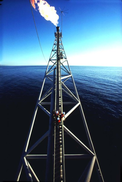 three-workers-venture-out-on-to-an-off-shore-rig's-torch