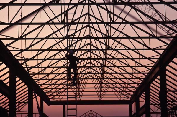 man climbing up ladder on building frame