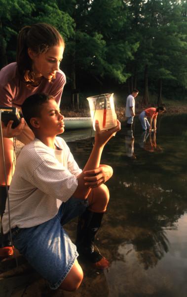 students-looking-into-beaker-at-lake-20932